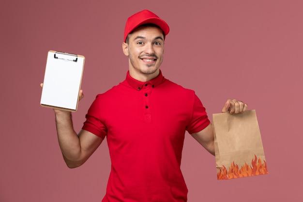 Вид спереди курьер-мужчина в красной форме и плаще, держащий пакет с едой и блокнот на розовой стене, униформа работника службы доставки