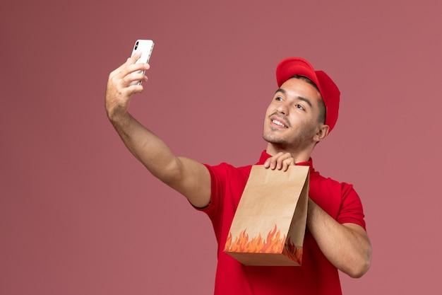 赤い制服を着た正面図の男性宅配便とフードパッケージを保持し、ピンクの壁にそれと一緒に自分撮りをしている岬