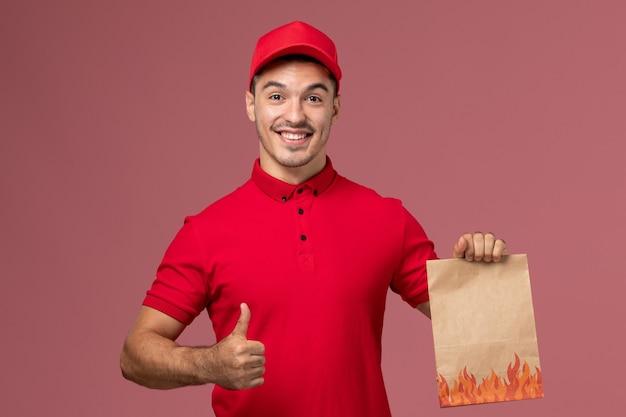 ピンクの壁に笑顔で食品パッケージを保持している赤い制服と岬の正面図男性宅配便