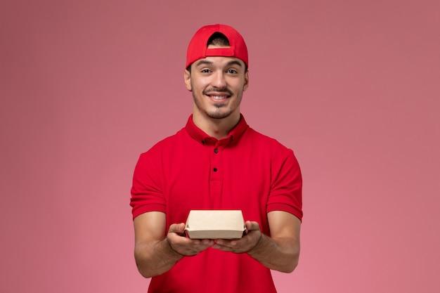 ピンクの背景に小さな配達パッケージを保持している赤い制服と岬の正面図男性宅配便。
