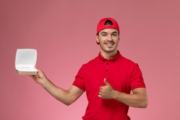 ピンクの背景に笑みを浮かべて小さな配達パッケージを保持している赤い制服と岬の正面図男性宅配便。