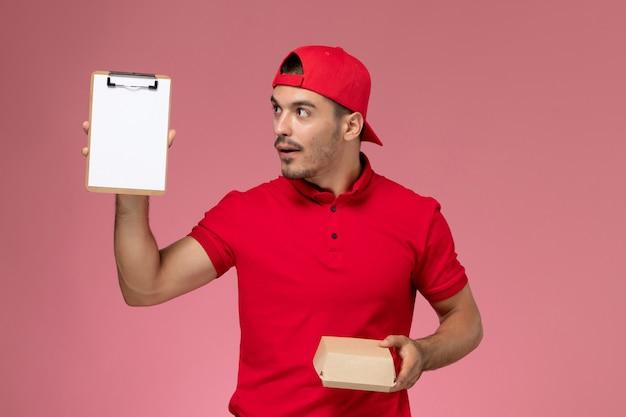 ピンクの背景にメモ帳付きの小さな配達パッケージを保持している赤い制服と岬の正面図男性宅配便。