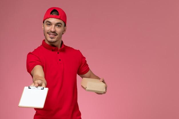 ピンクの背景に笑みを浮かべてメモ帳と小さな配達パッケージを保持している赤い制服と岬の正面図男性宅配便。