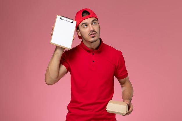 ピンクの背景にメモ帳を考えて小さな配達パッケージを保持している赤い制服と岬の正面図の男性の宅配便。