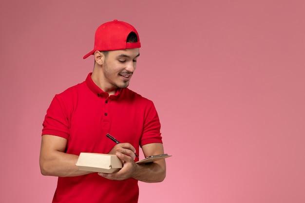 ピンクの背景にメモ帳を書く小さな配達パッケージを保持している赤い制服と岬の正面図の男性の宅配便。