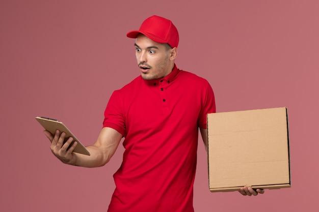 Вид спереди мужской курьер в красной форме и накидке, держащий блокнот с едой на розовой стене рабочего