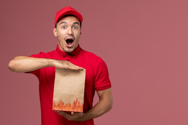 Курьер-мужчина, вид спереди в красной форме и накидке, держит бумажный пакет с едой и улыбается на розовом рабочем столе