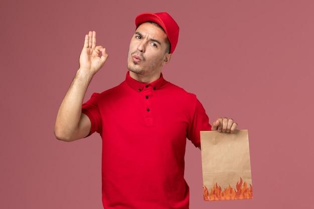 Курьер-мужчина в красной форме и накидке, держащий бумажный пакет с едой на розовом полу, вид спереди