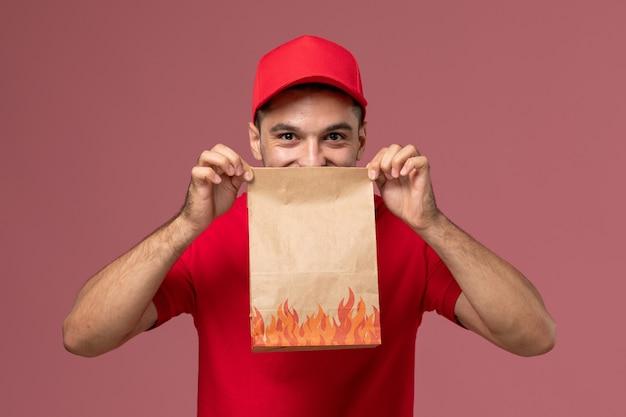 赤い制服を着た正面図の男性宅配便とピンクの壁に紙の食品パッケージを保持しているケープサービス配達男性の制服労働者