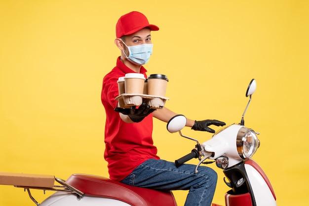 赤い制服を着た正面図の男性宅配便と黄色のジョブパンデミック共同フードサービスウイルスのコーヒーでマスク