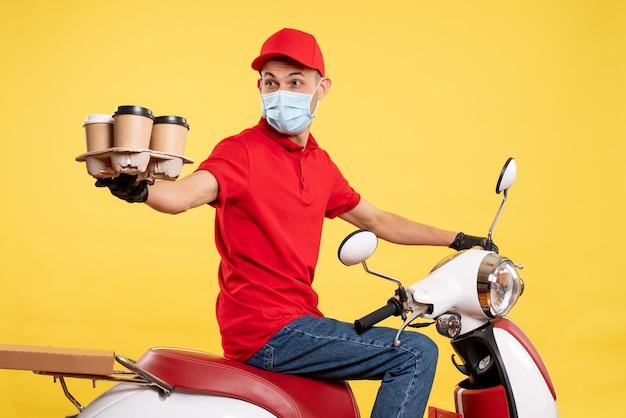 赤いユニフォームを着た正面図の男性宅配便と黄色の仕事のパンデミック配達共同フードサービスのコーヒーでマスク