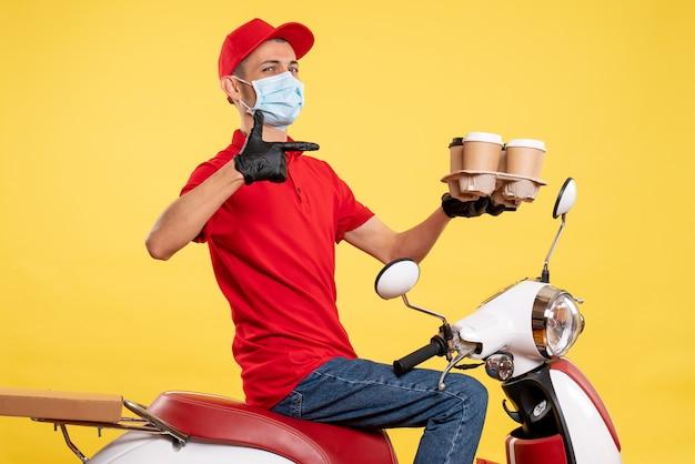 Курьер-мужчина, вид спереди в красной форме и маске с кофе на желтом цвете, работа, пандемия коронавируса - вирус общественного питания