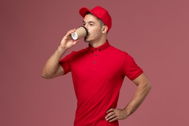 Курьер-мужчина в красной форме пьет кофе на розовой стене