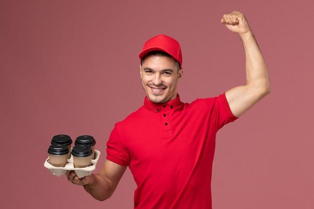 淡いピンクの壁の労働者に屈曲する茶色の配達コーヒーカップを保持している赤い制服の正面図男性宅配便