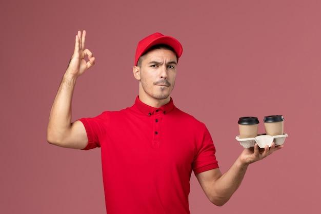 淡いピンクの壁の男性労働者に茶色の配達コーヒーカップを保持している赤い制服の正面図男性宅配便