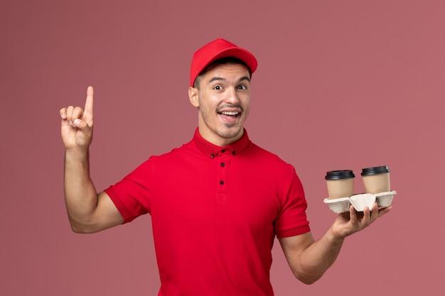 淡いピンクの壁の男性に茶色の配達コーヒーカップを保持している赤い制服の正面図男性宅配便