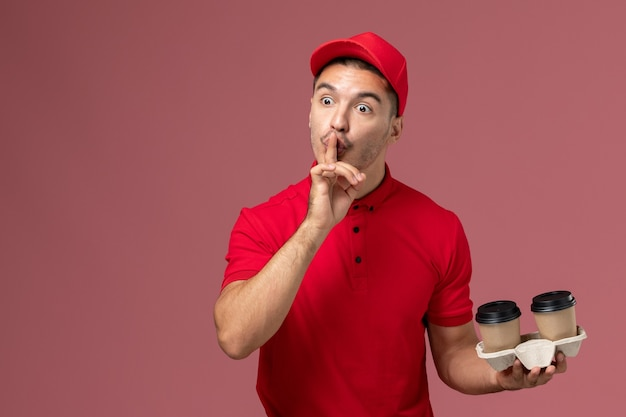 Вид спереди мужчина-курьер в красной форме держит коричневые кофейные чашки на розовой стене рабочий-мужчина