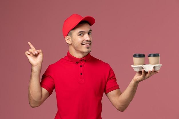 Курьер-мужчина в красной форме, держащий коричневые кофейные чашки на розовом столе