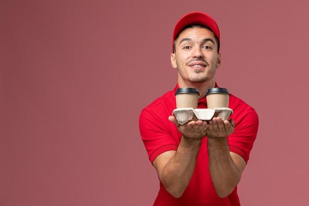 ピンクの壁の労働者に茶色の配達コーヒーカップを保持している赤い制服の正面図男性宅配便