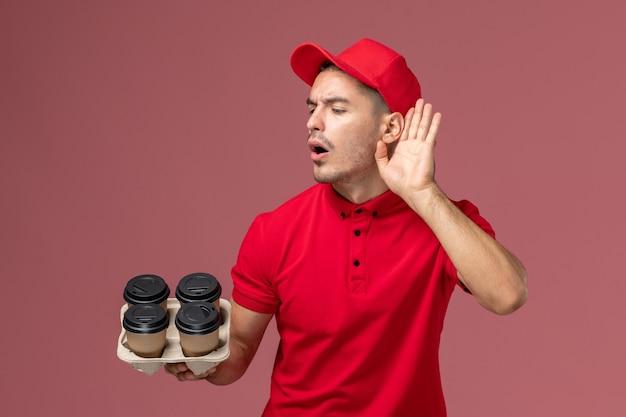 淡いピンクの壁の労働者に聞いてみようとしている茶色の配達コーヒーカップを保持している赤い制服を着た正面図の男性宅配便