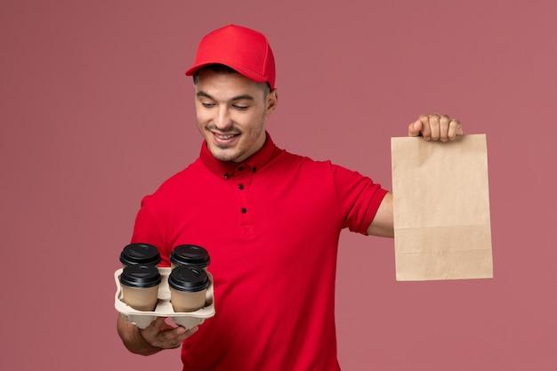ピンクの壁に食品パッケージと茶色の配達コーヒーカップを保持している赤い制服の正面図男性宅配便サービス配達労働者の制服