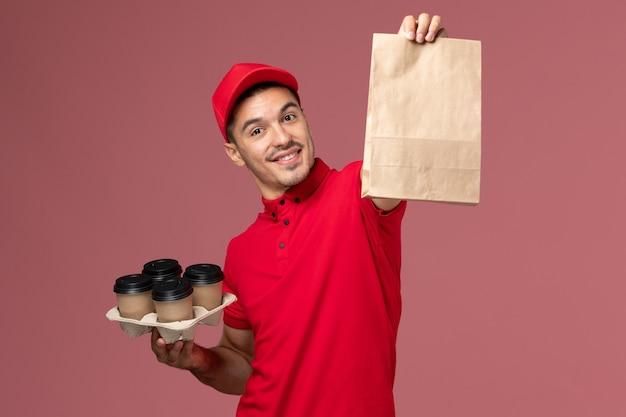 ピンクの壁に食品パッケージと茶色の配達コーヒーカップを保持している赤い制服の正面図男性宅配便