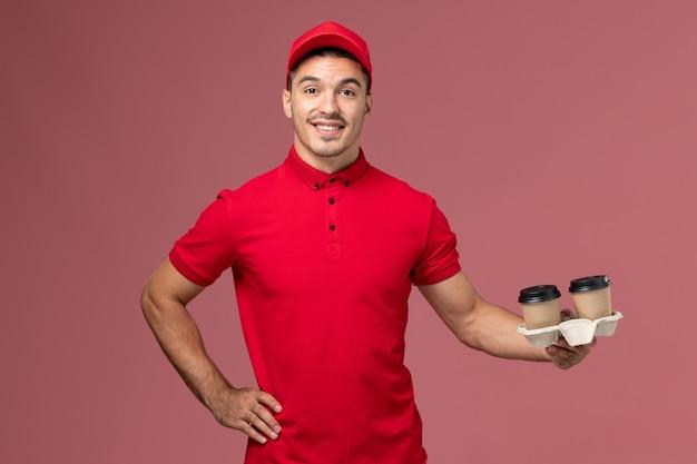 ピンクの壁のサービス配達労働者の制服の仕事に笑顔で茶色の配達コーヒーカップを保持している赤い制服の正面図男性宅配便