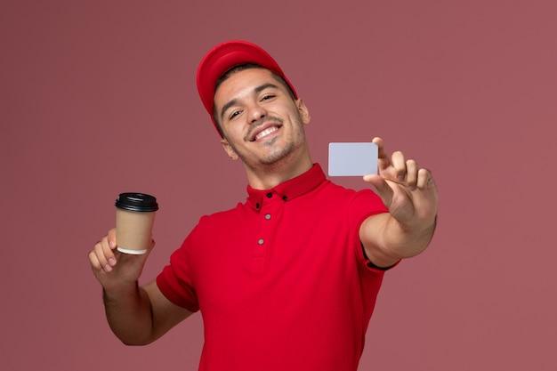 ピンクのデスクワーカーに配達コーヒーカップとカードを保持している赤い制服の正面図男性宅配便