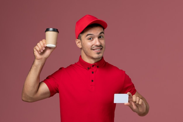 Курьер-мужчина, вид спереди в красной форме, держит чашку кофе с доставкой и открытку на розовой стене