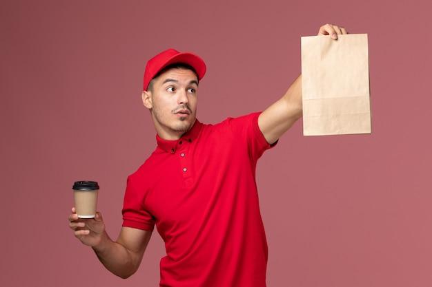 Вид спереди мужчина-курьер в красной форме, держащий чашку кофе и пакет с едой на светло-розовой стене, работник службы доставки в мужской униформе