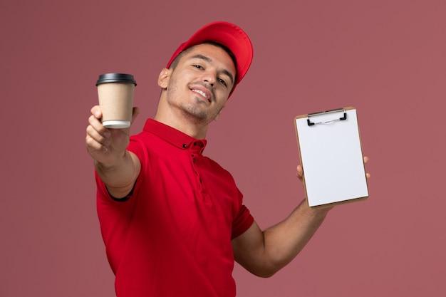 Вид спереди мужчина-курьер в красной форме, держащий чашку кофе и блокнот на розовой стене рабочий мужчина