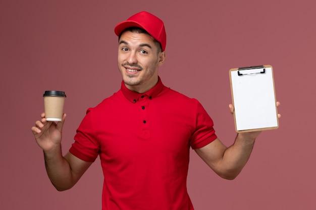 ピンクの壁の労働者の男性の仕事に配達コーヒーカップとメモ帳を保持している赤い制服の正面図男性宅配便