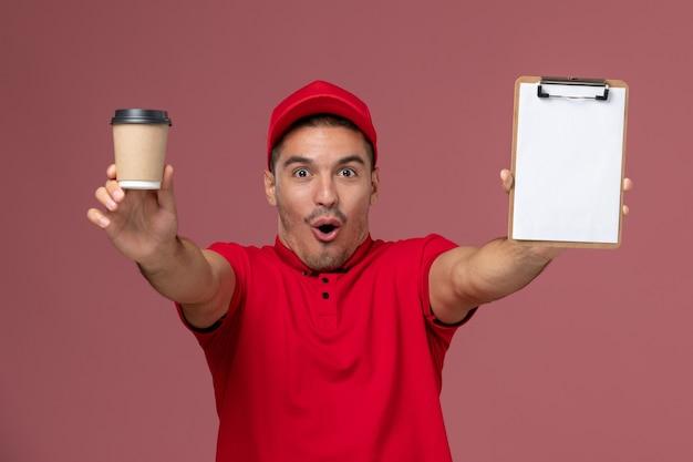 Вид спереди мужской курьер в красной форме, держащий чашку кофе и блокнот с забавным выражением лица на розовой мужской работе рабочего стола