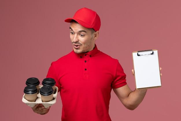 ピンクの壁にメモ帳と配達コーヒーカップを保持している赤い制服の正面図男性宅配便