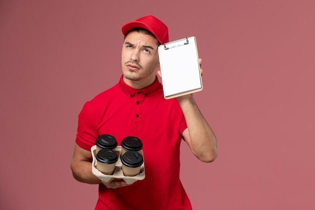 ピンクの壁にメモ帳を考えて配達コーヒーカップを保持している赤い制服の正面図男性宅配便