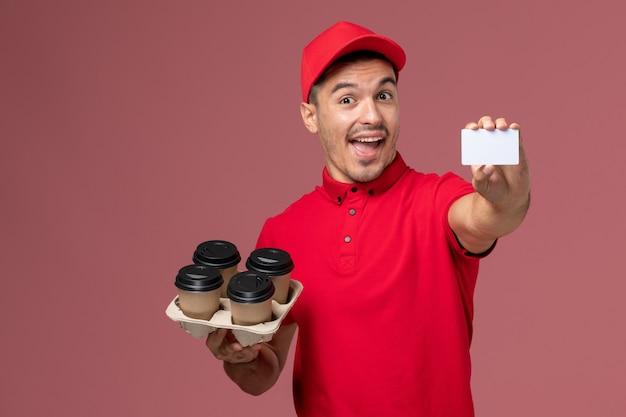 ピンクの壁のサービスの仕事の配達労働者の制服に白いカードと配達コーヒーカップを保持している赤い制服の正面図男性宅配便