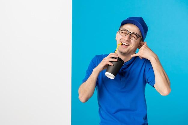 Вид спереди мужской курьер в униформе, пьющий доставку кофе на синем