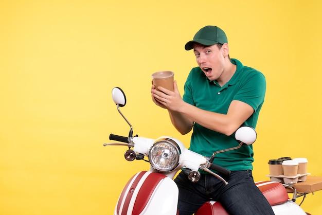 黄色のコーヒー カップを保持している制服を着た正面の男性宅配便