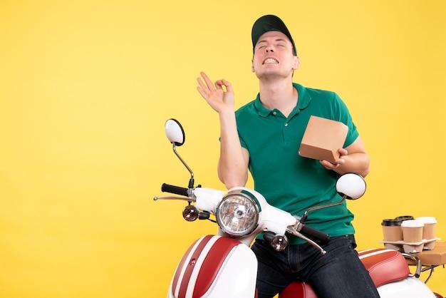 黄色の小さな食品パッケージを保持している制服を着た正面の男性宅配便