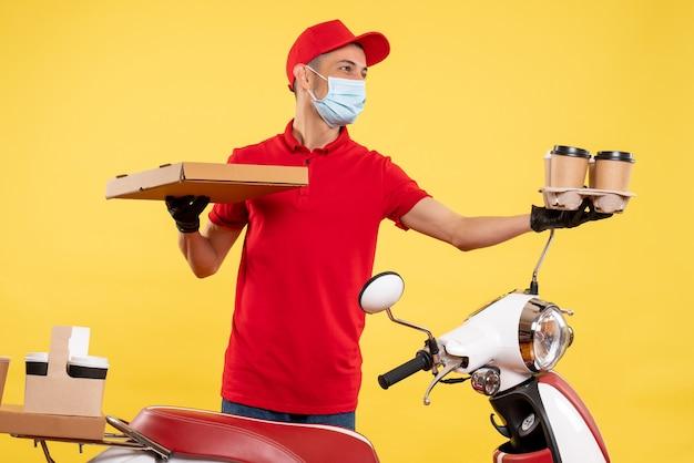 黄色のパンデミックサービスの仕事でコーヒーとフードボックスと制服を着た正面図の男性の宅配便は、制服の仕事のウイルスの色をcovid