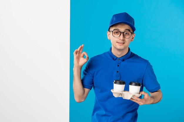 Вид спереди мужской курьер в форме с кофе на синем