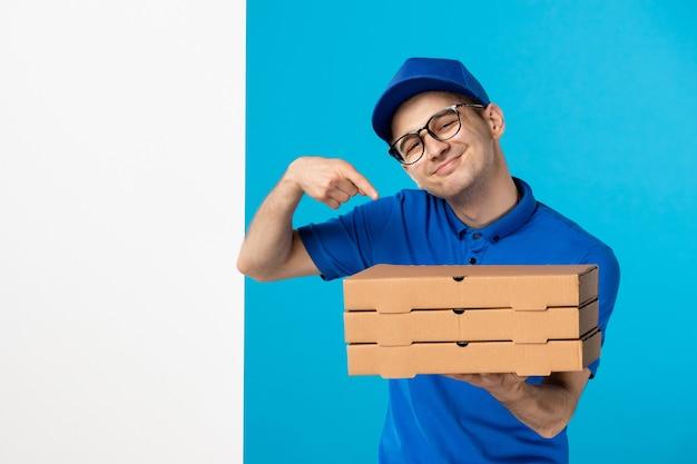 Вид спереди мужской курьер в униформе с коробками для пиццы на синем
