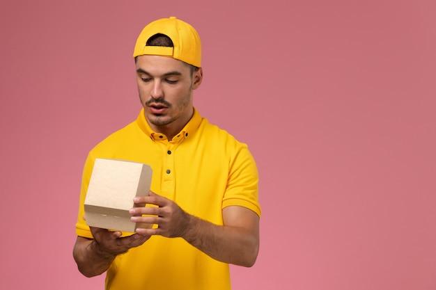 黄色のユニフォームとケープを保持し、ピンクの背景に小さな配達食品パッケージを開いている正面図の男性の宅配便。