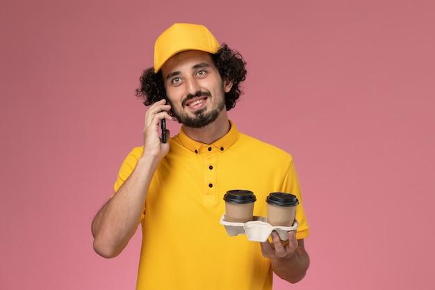 ピンクの壁に電話で話している黄色の制服と茶色の配達コーヒーカップを保持している岬の正面図男性宅配便