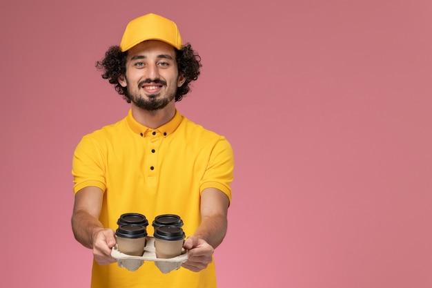 ピンクの壁に茶色の配達コーヒーカップを保持している黄色の制服と岬の正面図男性宅配便