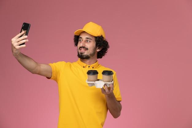 ピンクの壁に写真を撮る黄色の制服と茶色の配達コーヒーカップを保持している岬の正面図男性宅配便