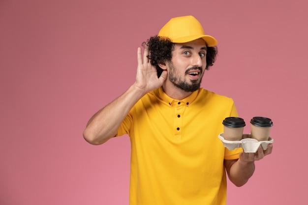 Курьер-мужчина в желтой униформе и плаще, держащий коричневые кофейные чашки, пытается выслушать на розовой стене