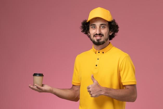 ピンクの壁に配達コーヒーカップを保持している黄色の制服と岬の正面図男性宅配便