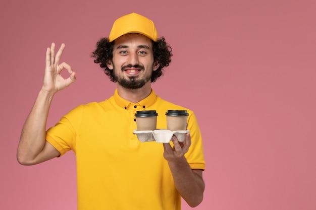 ピンクの壁にポーズをとって配達コーヒーカップを保持している黄色の制服と岬の正面図男性宅配便