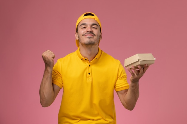 ピンクの背景で応援している小さな配達食品パッケージを保持している黄色の制服と岬の正面図の男性の宅配便。